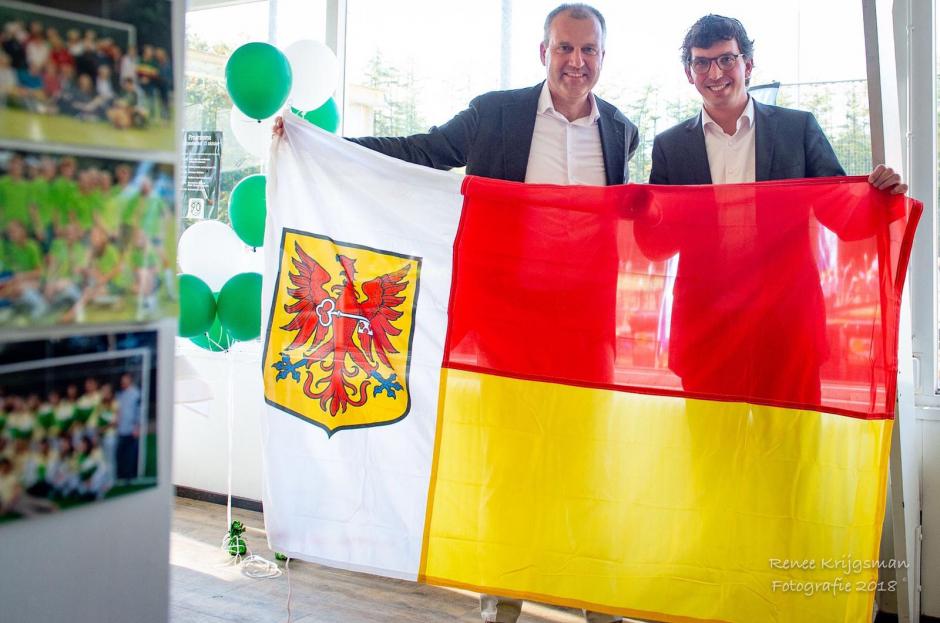 Wethouder Nathan Stukker overhandigt het kado van de gemeente, de vlag van Apeldoorn, aan voorzitter Edgar Breed